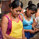 Chocolate making is a social activity for members of the Red de Mujeres who husk roasted cacao beans together.