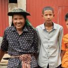 Cheang Sophat, left, and wife Hem Champa, far right, were able to send their second child to college after earning more money from vegetables grown in a nethouse. The couple is confident they will be able to send their third child, 14-year-old Phat Daroth, second from right, to college as well. (Max Fannin for UC Davis)